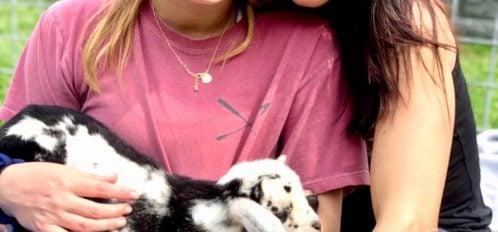 girls holding baby goat