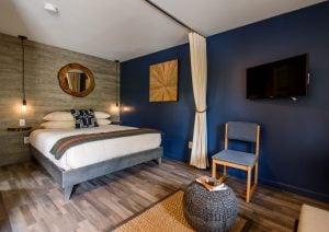 bedroom with queen bed, flat screen tv, chair, artwork