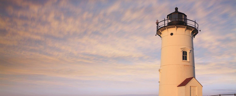 nobska lighthouse on cape cod with purple sunset sky