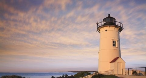 nobska lighthouse on cape cod with purple sunset sky