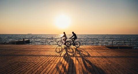 two people riding bikes on boardwalk near ocean, woods hole bike path